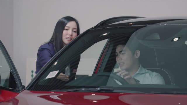 asian saleswoman introducing customer to test drive in showroom - test drive stock videos & royalty-free footage