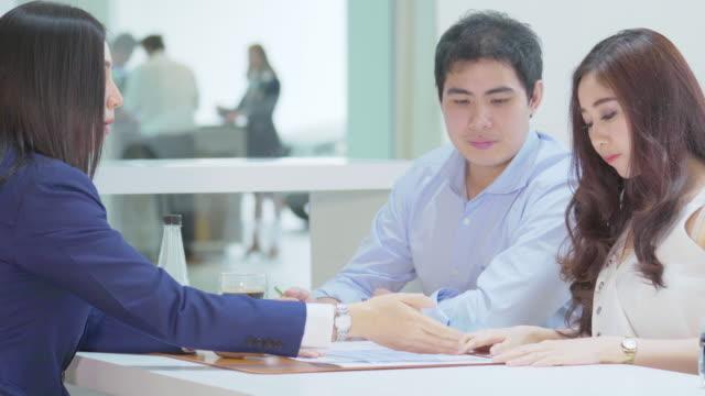 販売の契約に署名するカップルの顧客を紹介するアジアのセールスウーマン - 署名する点の映像素材/bロール