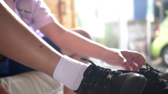 asian schoolboy in uniform wearing socks, shoes and tights his shoelaces at home with sunlight in the morning, lifestyle concept. - tights stock videos & royalty-free footage