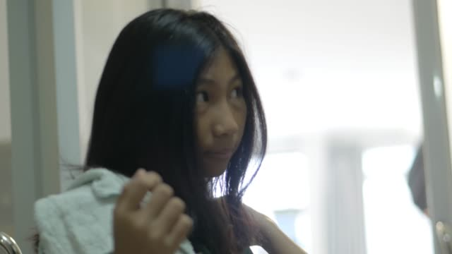 asian schoolgirl in uniform brushing her hair and tie bow before go to school by herself, lifestyle concept. - hair bow stock videos & royalty-free footage
