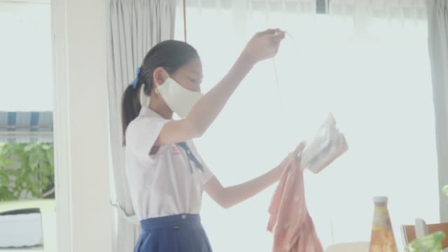 asian schoolgirl in uniform wearing face mask and shoulder bag before go to school in the morning. - shoulder bag stock videos & royalty-free footage