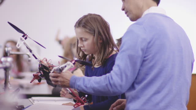 Asian Science Teacher Examining a Drone with an Elementary-Age Student