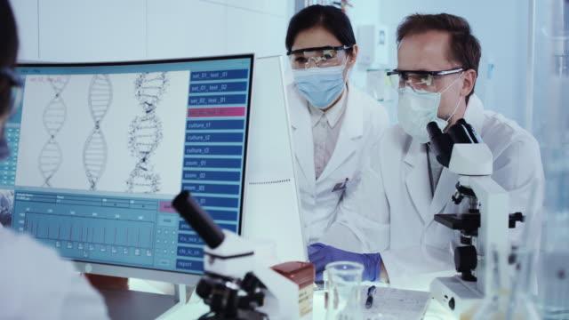 vídeos de stock e filmes b-roll de asian scientist studying dna mutations. research partner in background - mutação genética