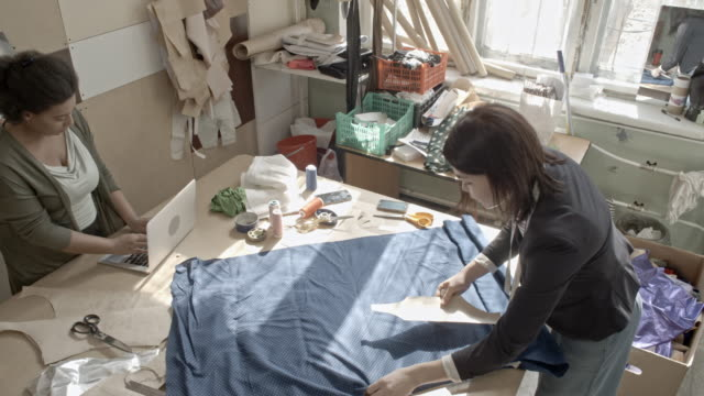 asian seamstress outlining sewing pattern on fabric - パタンナー点の映像素材/bロール