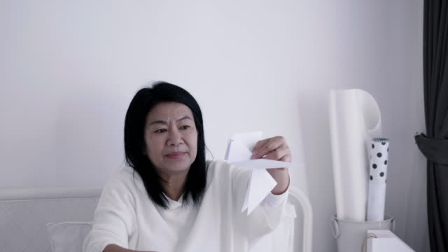 Asian senior adult is doing paper craft to create bird for her leisure activity at home