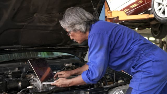 asian senior auto mechanic check condition of engine and electric system ,record on the list.check engine oil level,check electric fuse.used computor diagnosis damage of engine. - motor vehicle stock videos & royalty-free footage