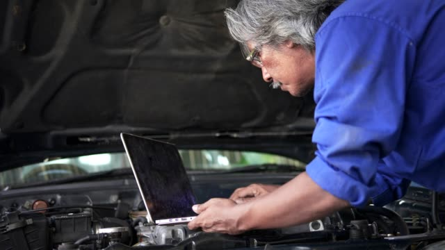 asian senior auto mechanic check condition of engine and electric system ,record on the list.check engine oil level,check electric fuse.used computor diagnosis damage of engine. - guidance stock videos & royalty-free footage