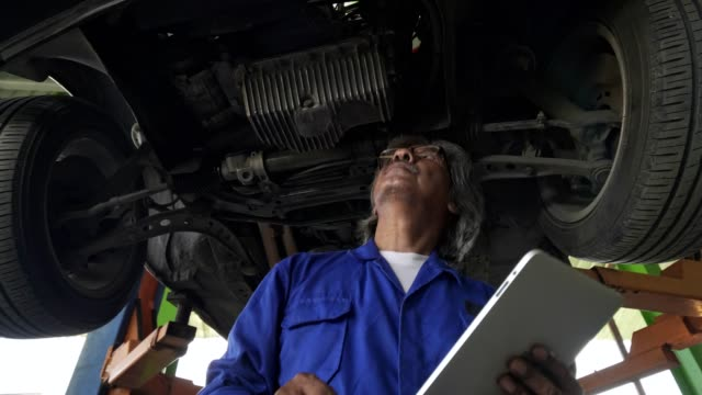 asian senior auto mechanic check condition of engine and electric system ,record on the list.check engine oil level,check electric fuse.checking oil leak and suspension underneat car.used tablet record and checking damage of suspension. - hydraulic platform stock videos & royalty-free footage