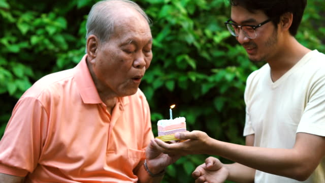 asian senior blowing candle held by grandson, outdoor - life events stock videos & royalty-free footage