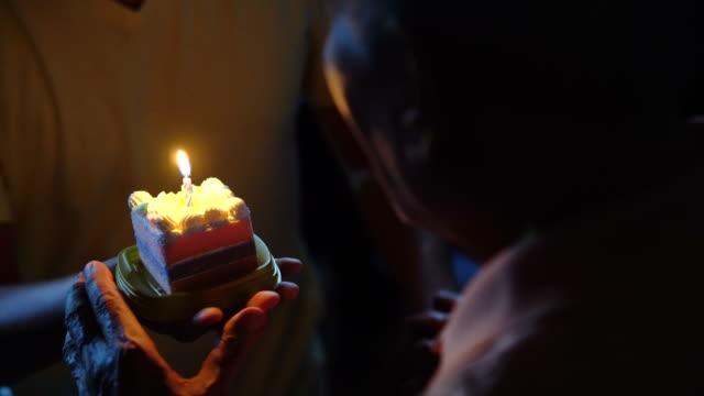 vídeos de stock e filmes b-roll de os asian senior blowing candle held by grandson - soprar
