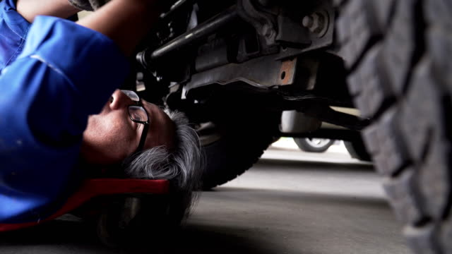 Asian senior car mechanic laying down and move to under vehicle