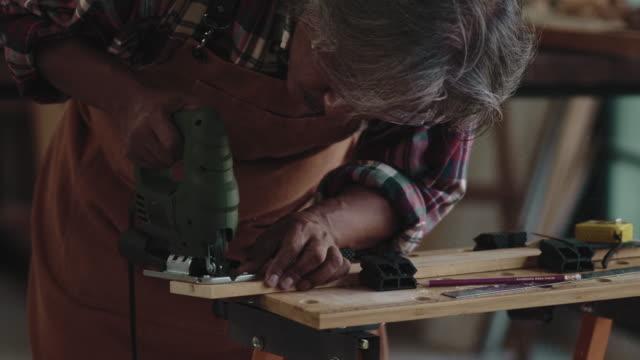 vídeos de stock e filmes b-roll de asian senior carpenter at studio - camisa com botões