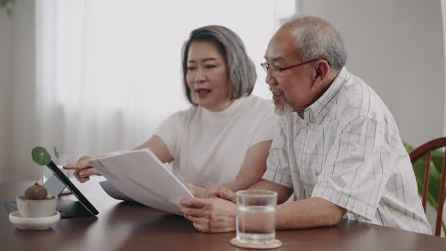 オンライン支払いのために国内手形を計算するアジアのシニアカップル - 税金点の映像素材/bロール