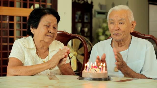 Asian senior couple celebrate happy birthday in living room