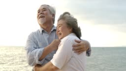 Asian senior couple embracing each other on the beach in slow motion.