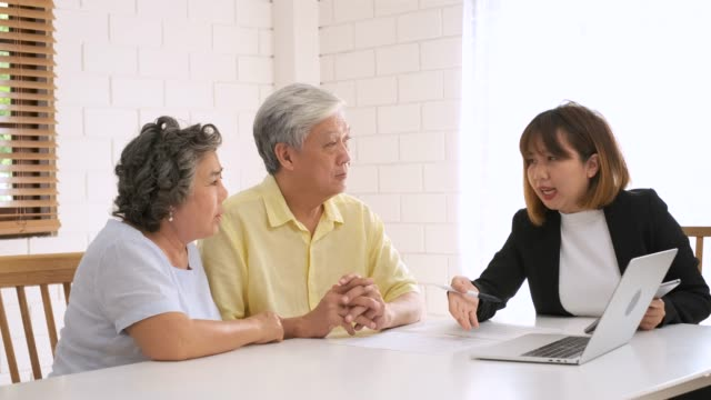 asian senior couple get advice from financial planner at home.aging at home. - southeast asian ethnicity stock videos & royalty-free footage