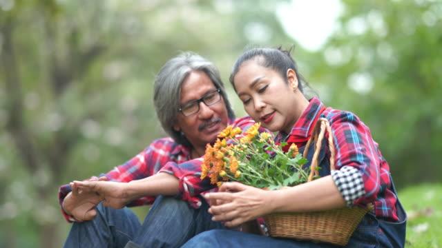 vídeos y material grabado en eventos de stock de pareja senior asiático creciendo flores juntos en el jardín - 65 69 años