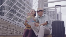 Asian Senior couple holding map to search for destinations streets in Thailand,  After the retirement age seniors traveling with their own savings, Travelers and lifestyle of Older concept