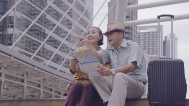asian senior couple holding map to search for destinations streets in thailand,  after the retirement age seniors traveling with their own savings, travelers and lifestyle of older concept - coniugi video stock e b–roll