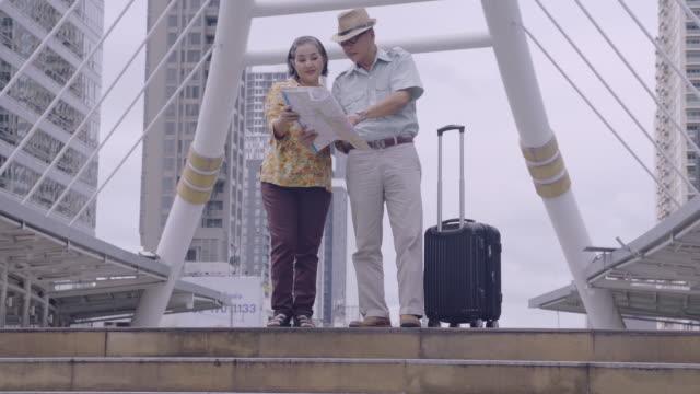 タイの目的地を探す地図を持つアジアのシニアカップル、定年退職後、自分の貯蓄で旅行する高齢者、旅行者と古い概念のライフスタイル - リタイアメント点の映像素材/bロール