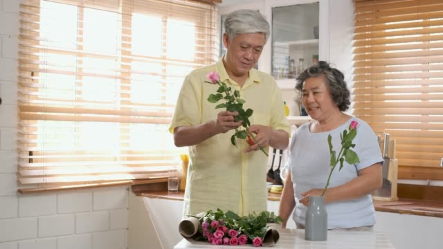 asian senior couple husband and wife flower arrangement to vase on table in kitchen at home in valentine's day.lovely senior couple concept. - flower arrangement stock videos and b-roll footage