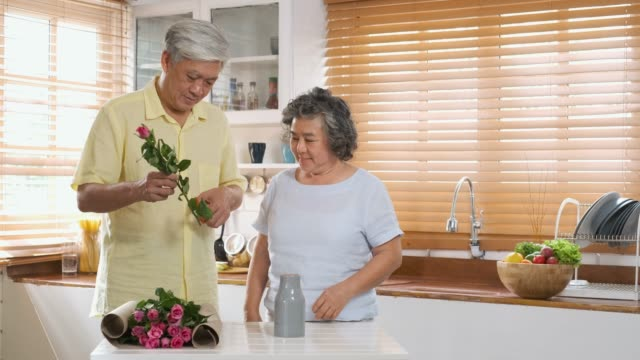 asian senior couple husband and wife flower arrangement to vase on table in kitchen at home in valentine's day.lovely senior couple concept - flower arrangement stock videos and b-roll footage