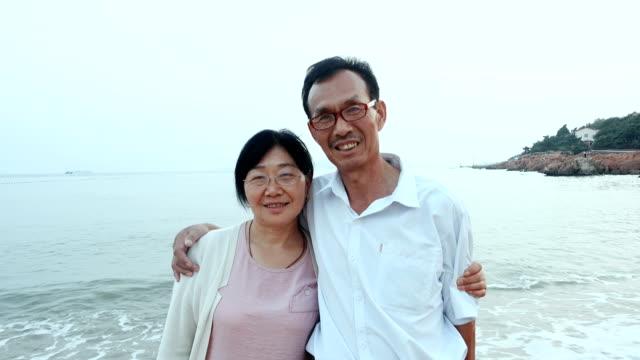 Asian senior couple looking at camera
