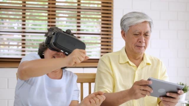 vídeos y material grabado en eventos de stock de asiática senior pareja jugar virtual realtiy gafas auriculares y la tableta de ver vídeo vr y divertirse juntos en la sala de estar en casa. senior con tecnología. crianza en casa. - miembro humano