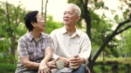 Asian senior couple showing affectionate and care through a cup of coffee in morning bright natural park