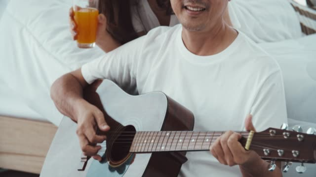 vídeos y material grabado en eventos de stock de pareja senior asiática cantando juntos - guitarra