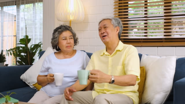 asian senior couple talking and drink coffee together and sitting at sofa in living room at home.senior retirement lfietyle.aging at home concept. - coffee drink stock videos & royalty-free footage