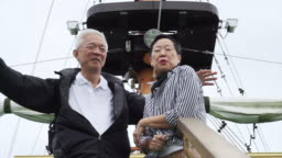 Asian senior couple travel and have boat cruising in beautiful lake