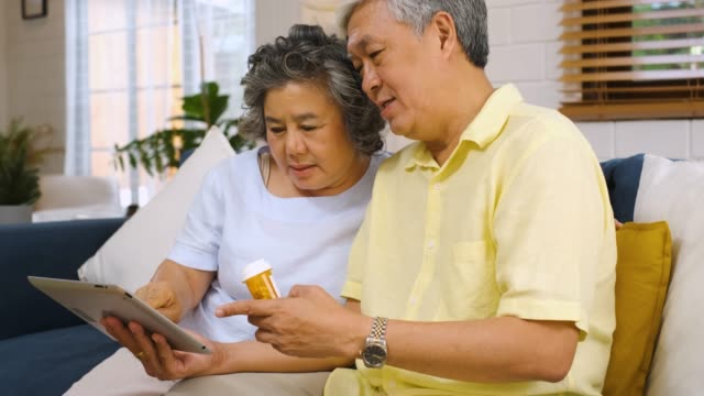 asian senior couple use tablet computer searching about doctor pill sitting on sofa at home,senior learn to use technology. - prescription medicine home stock videos & royalty-free footage