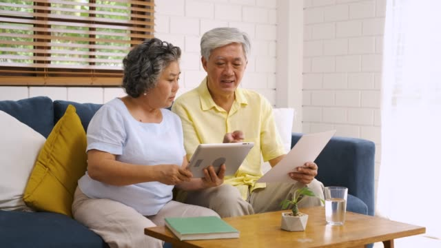 asian senior couple use tablet searching about retirement financial document sitting on sofa at home,senior learn to use technology.aging in place concept - retirement stock videos & royalty-free footage