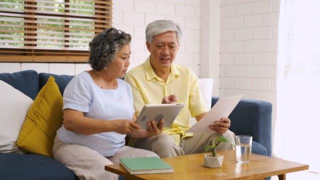 stockvideo's en b-roll-footage met aziatische senior paar gebruik tablet zoeken over pensionering financieel document zittend op sofa thuis, senior leren om technologie te gebruiken. veroudering in plaats concept - retirement