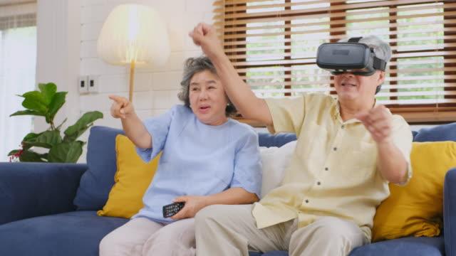 stockvideo's en b-roll-footage met aziatische senior paar met behulp van virtual reality bril en afstandsbediening zittend op de bank thuis te houden. senior gelukkig moment - interactief
