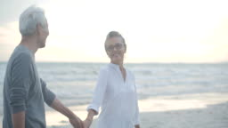 Asian senior couple walking and talking on beautiful tropical beach in slow motion.