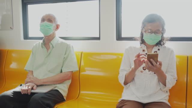 asiatische senior paar tragen schützende gesichtsmaske mit telefon im zug - passenger train stock-videos und b-roll-filmmaterial