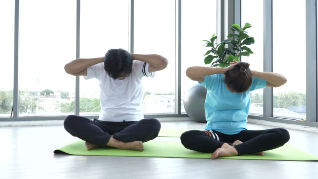 vídeos y material grabado en eventos de stock de parejas de la tercera edad asiáticas haciendo meditación de yoga para hacer ejercicio en casa - músculo humano