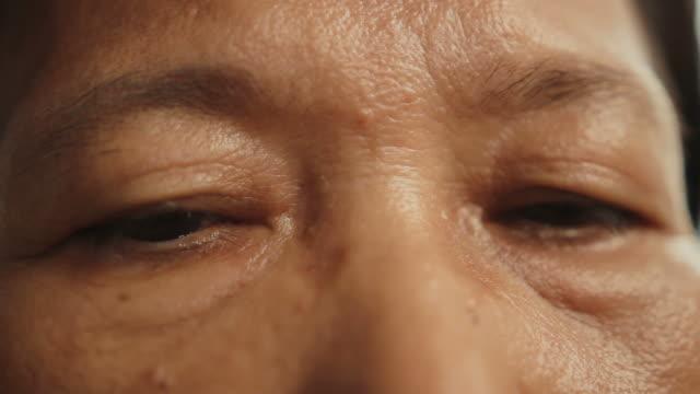 asian senior eyes close up - blinka ansiktsuttryck bildbanksvideor och videomaterial från bakom kulisserna