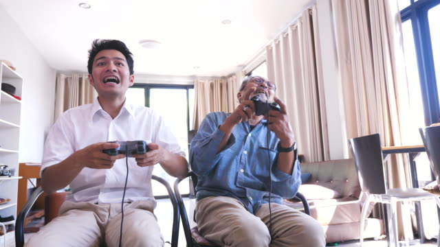 asian senior father and his adult son enjoy playing video games together in living room at home - retirement stock videos & royalty-free footage