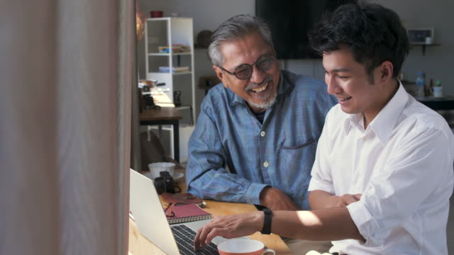 asian senior father and his adult son using laptop computer while sitting at home - two generation family stock videos & royalty-free footage