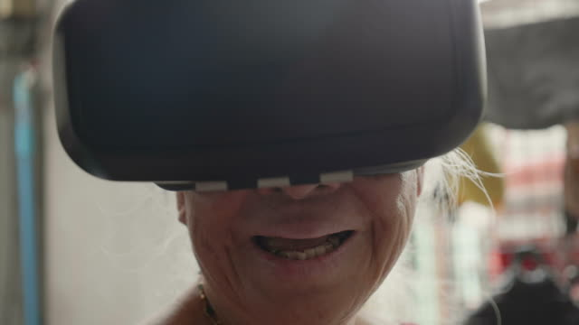 Asian Senior female have fun and wearing virtual reality glasses.