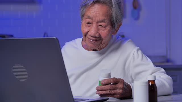 asian senior grandmother age 83 yearold listening to healthcare worker explaining medicine to her by computer in home at night during social distancing.senior health technology concept. - health technology stock videos & royalty-free footage