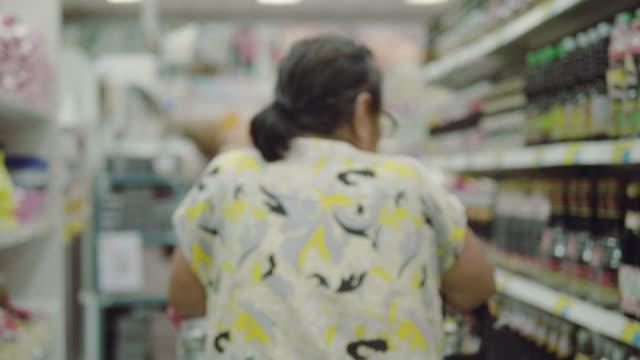 vídeos de stock, filmes e b-roll de compras de mercearia sênior asiática - etiqueta mensagem
