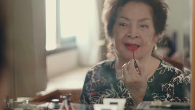 vidéos et rushes de dame senior asiatique appliquer le rouge à lèvres - miroir ancien