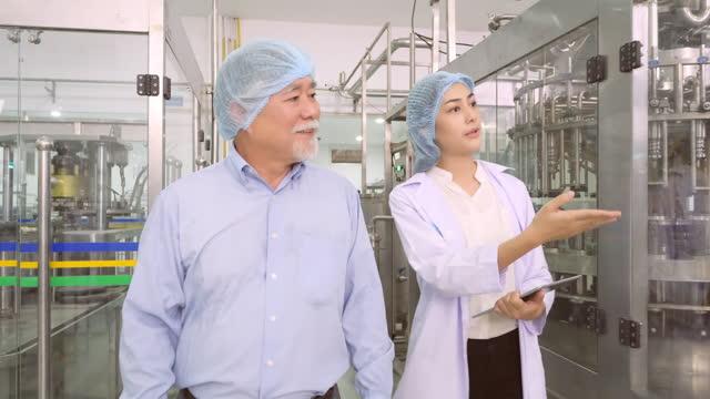 asian senior männlich alter 65jahre alt und weibliche ingenieur überprüfung der arbeitsprozess der industriellen produktionslinie von kohlensäurehaltigen getränke planke. der herstellungsprozess von getränken in der fabrik. unterstützende männchen - connection in process stock-videos und b-roll-filmmaterial