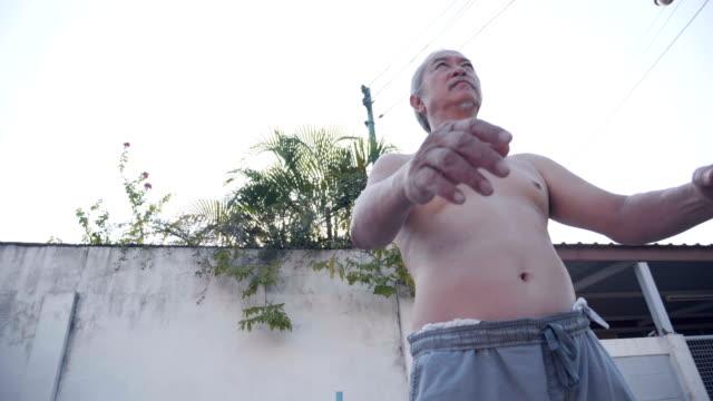 vídeos y material grabado en eventos de stock de ejercicio diario de hombre mayor asiático. - entrenamiento sin material
