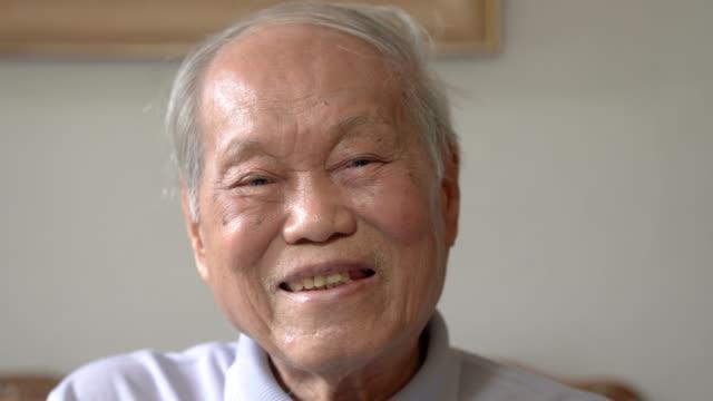 cu asian senior man directly smile at camera - senior men stock videos & royalty-free footage