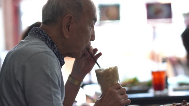 asian senior man drinking ice smoothie  from straw , retirement concept - lunch stock videos & royalty-free footage